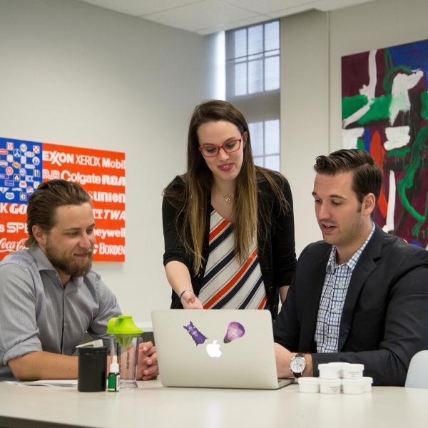 Image displays business advisor helping students.