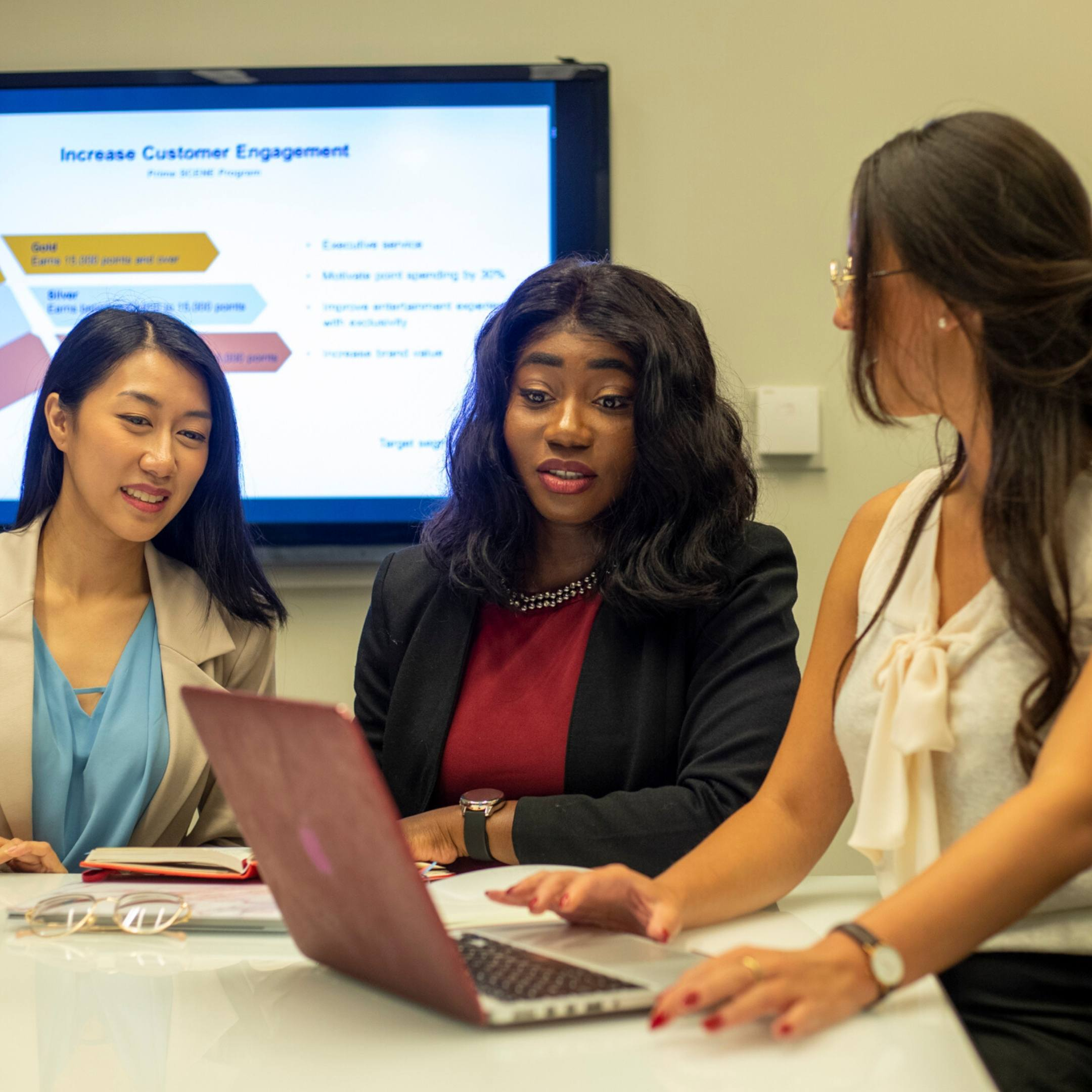 Image of three females working and brainstorming in a meeting.